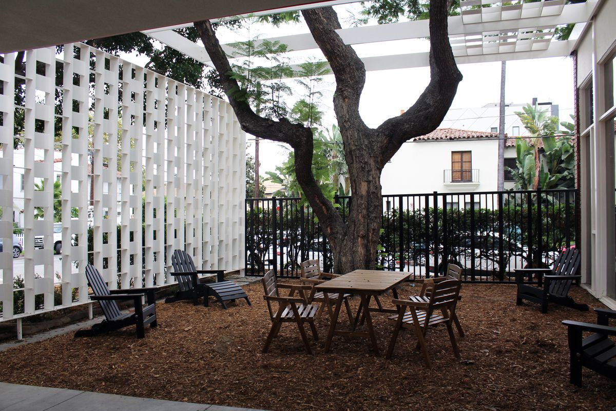 Outdoor seating area with a wooden table, chairs and lounging chairs available for future tenants.