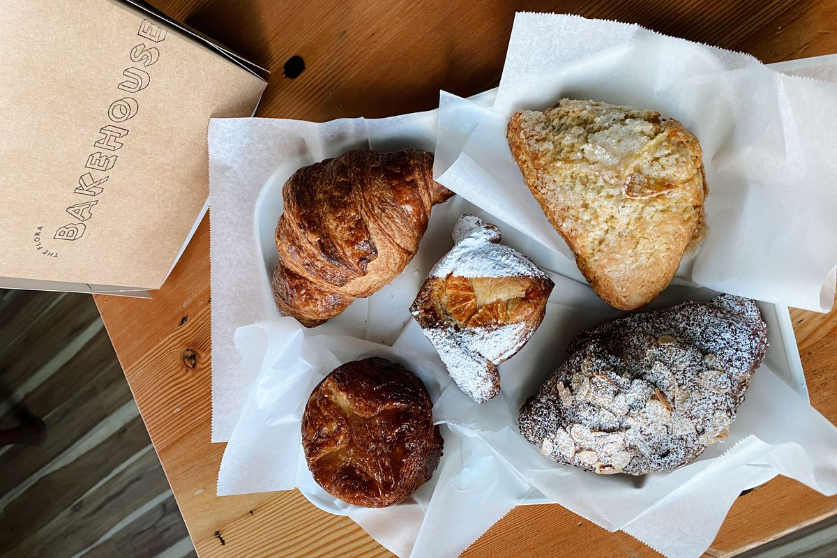 """A selection of five baked goods — including a muffin and scone —on a wood table, next to a sign that says """"Bakehouse"""""""