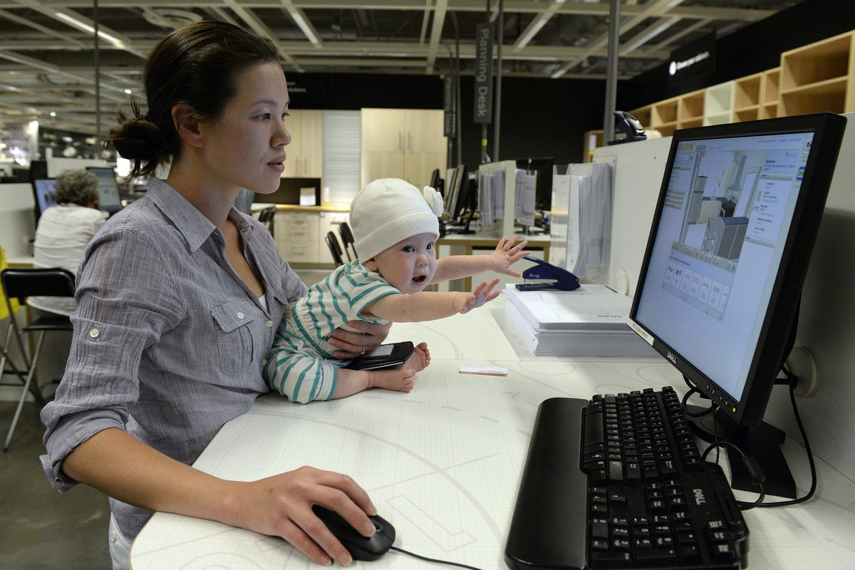 Mom Sarah Haigney and 11-month-old daughter Lana Haigney use the computer at IKEA's kitchen design space at its Centennial store on Thursday, August 28, 2014.