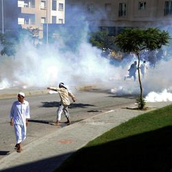 """Demonstrators throw stones during a protest against the anti-Islam film """"Innocence of Muslims"""" outside the U.S. Embassy in Tunis, Tunisia, as police respond with tear gas Friday, Sept. 14, 2012. Protests against he film spread to their widest extent yet around the Middle East and other Muslim countries Friday, as protesters smashed into the German Embassy in the Sudanese capital and security forces in Egypt and Yemen fired tear gas and clashed with protesters to keep them away from U.S. embassies."""