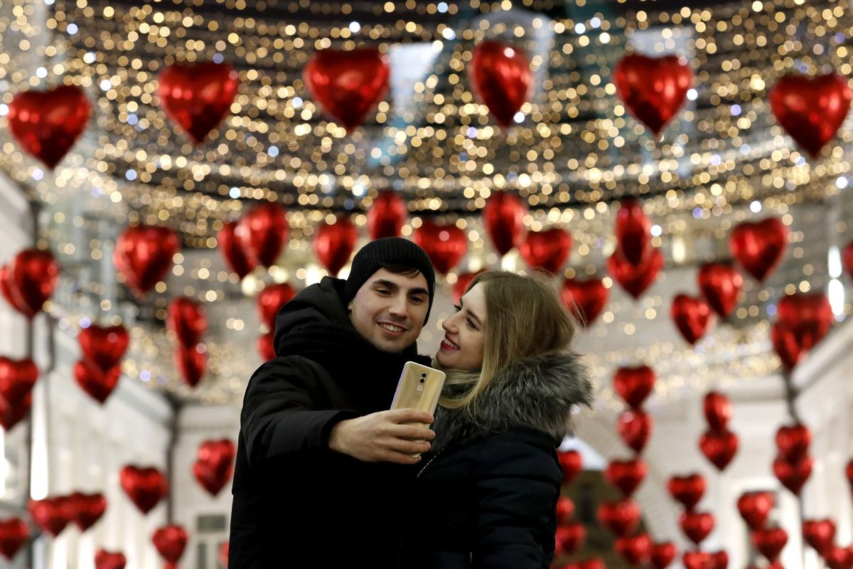 A couple taking a selfie in front of a display of hearts and gold glitter.