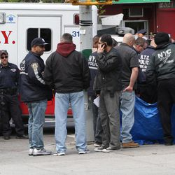 A crime scene unit officer, second from left, holds a bag with evidence as other investigate over the body of a robbery suspect behind the blue tarp at a crime scene in the East Harlem neighborhood of Manhattan, Thursday, April 12, 2012 in New York.  An armed bandit was killed Thursday during a chaotic getaway following a robbery at an East Harlem pharmacy of prescription painkillers and cash, police said.