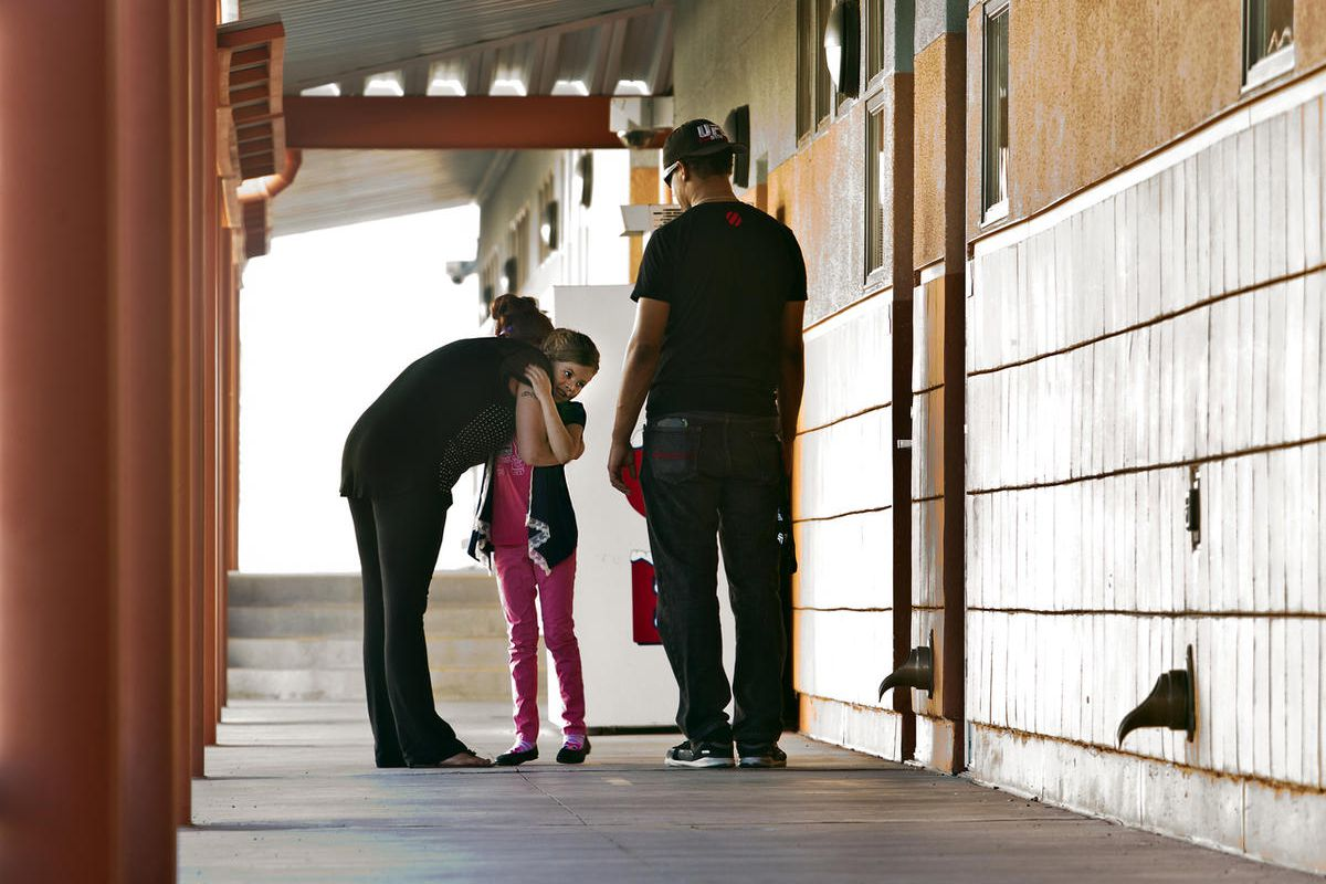 Shana Hairston hugs her daughter Natasha goodbye as husband Michael Hairston Jr., right, stands by at Sandy Valley School on Sept. 24, 2015, in Sandy Valley, Nevada. People like Hairston have been pushing the Clark County School District to honor a plan t