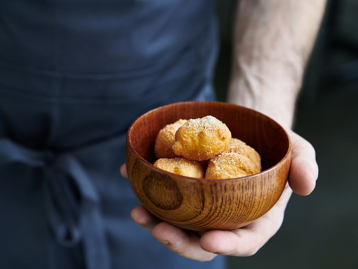 The hand of chef Justin Woodward holds a bowl of cheesy beignets at Ok Omens