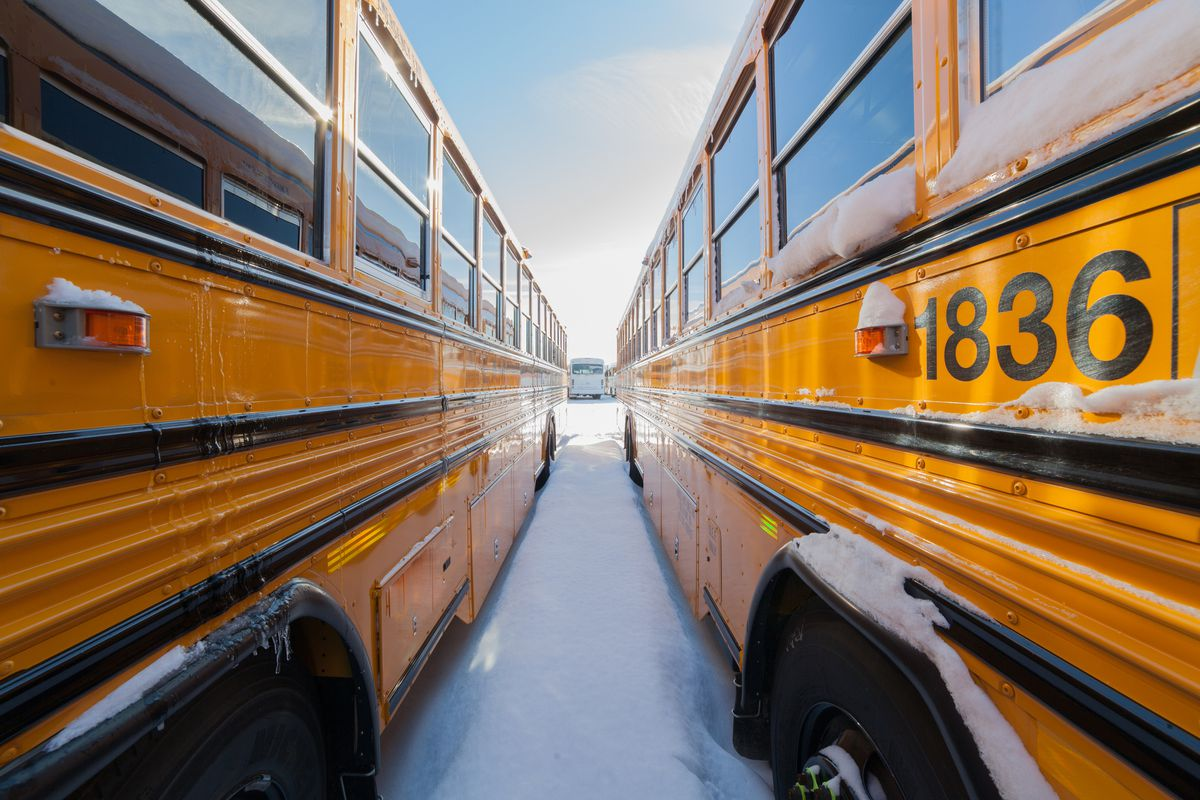 School buses in a school bus yard in winter with snow.