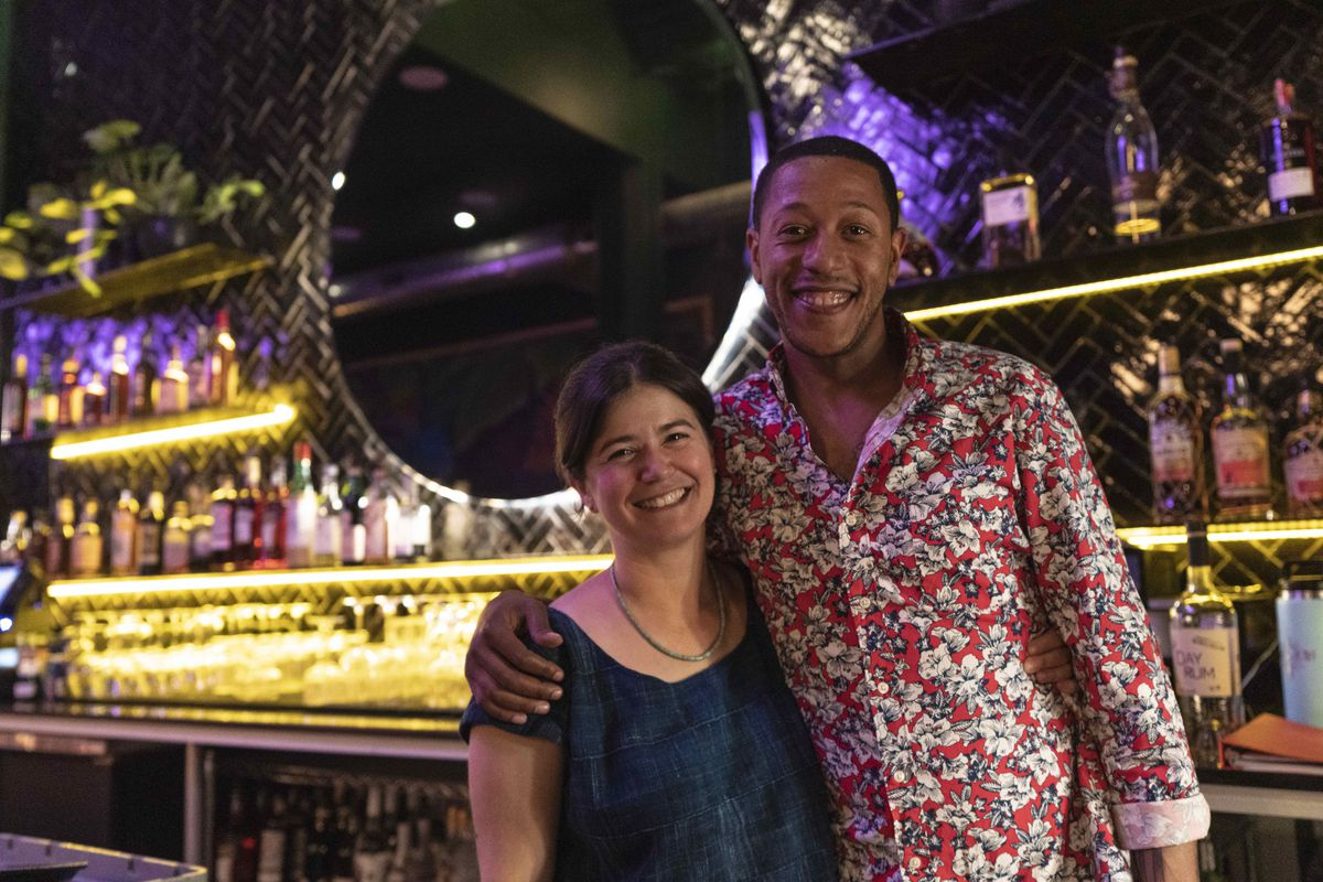 Alex Maynard (right) in a a long-sleeved floral shirt, pictured here standing in front of the bar at Sobre Mesa with fellow bar consultant Susan Eggett
