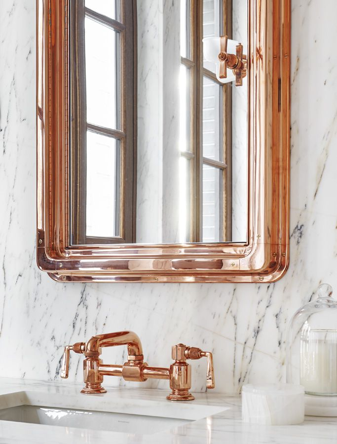 The master bathroom features marble slab walls and custom copper faucets.