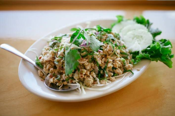 A white plate holds ground meat topped with sprigs of cilantro and garnished with cucumber slices on a leaf of lettuce.