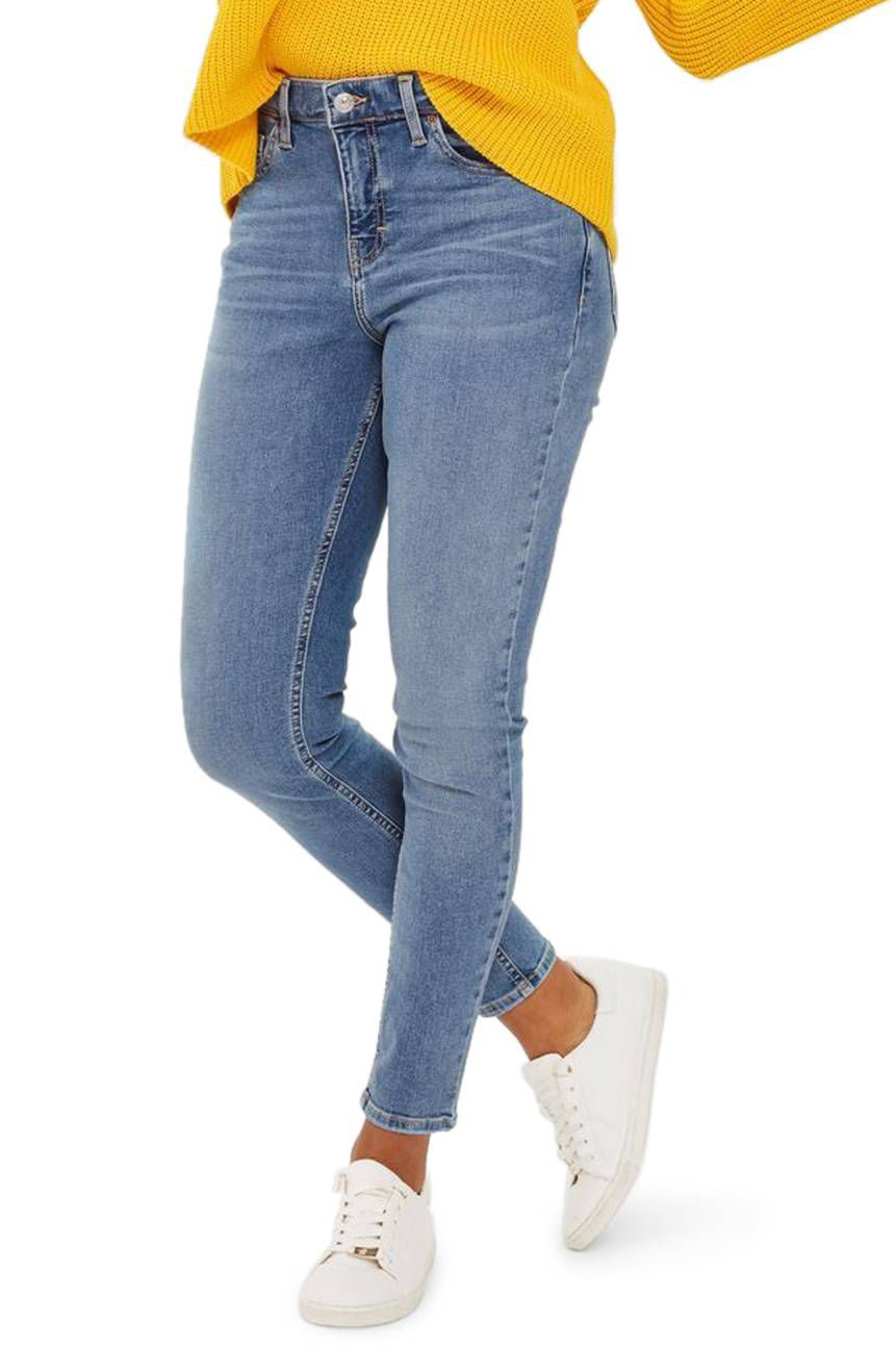 A model in blue skinny jeans and white sneakers