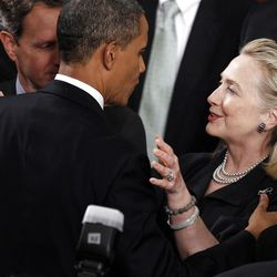 FILE - In this Jan. 24, 2012, file photo Secretary of State Hillary Rodham Clinton greets President Barack Obama after he delivered his State of the Union address on Capitol Hill in Washington. Once a tense rivalry, the relationship between Obama and the Clintons has evolved into a genuine political and policy partnership. Partially visible at left is Treasury Secretary Treasury Secretary Timothy Geithner. (AP Photo/Evan Vucci, File)