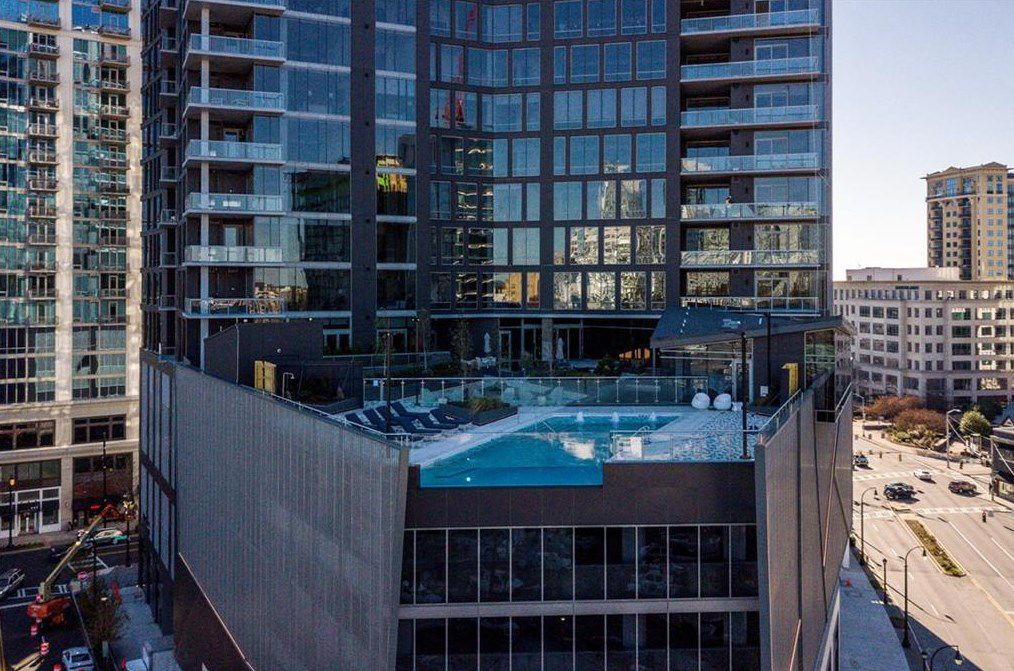 A tall glassy condo building with a pool with a glass wall.