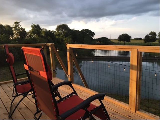 The deck on a shipping container home. There are two red lounge chairs looking out onto a lake.