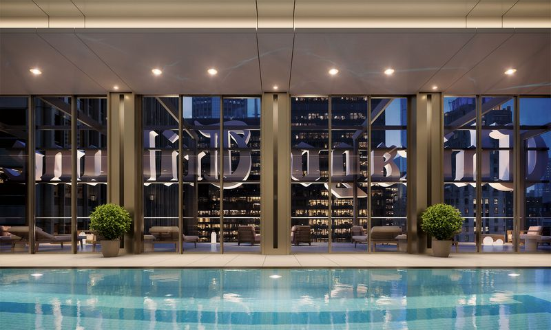A night time view of an indoor pool with recessed lighting, blue water, two potted plants, scatted comfortable lounge chairs and reverse signage that says 'Chicago Tribune' on the exterior of the building.