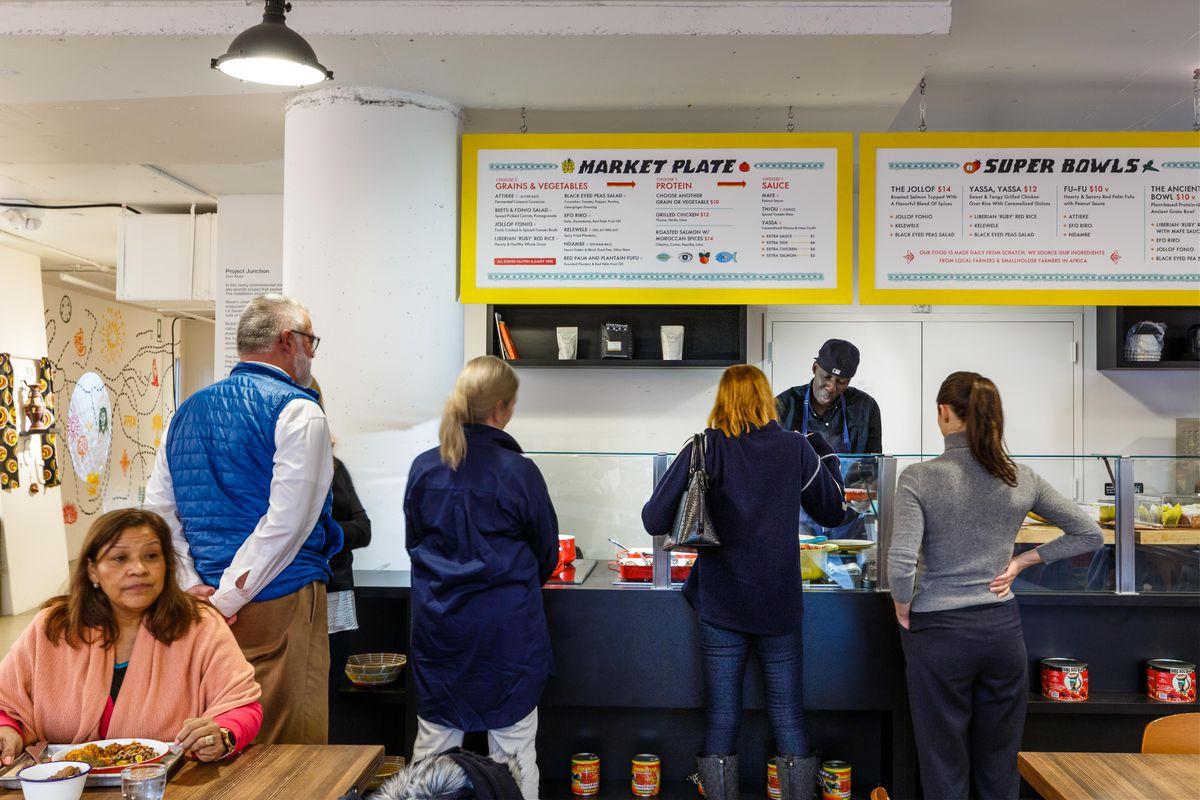 Patrons line up at the counter at Teranga, while yellow menus hang above them