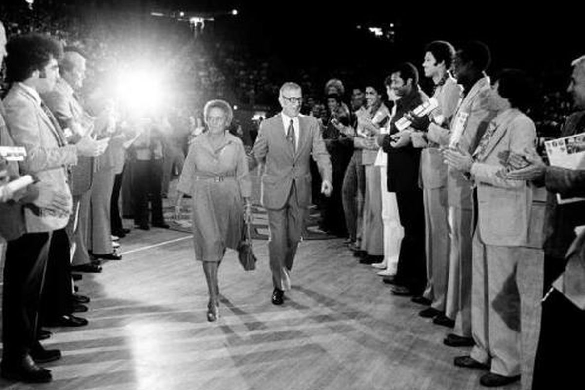 <em><strong>Coach</strong> walks with <strong>Nell</strong>, as they pass between former Bruin players in a birthday salute to the retiring <strong>Coach</strong> at Pauley in October, 1975. Photo Credit: Associated Press</em>