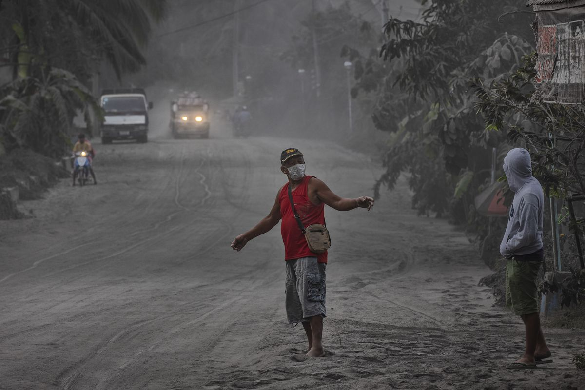 Residents walk along a road covered in volcanic ash from Taal Volcano's eruption on January 13, 2020 in Lemery, Batangas province, Philippines.