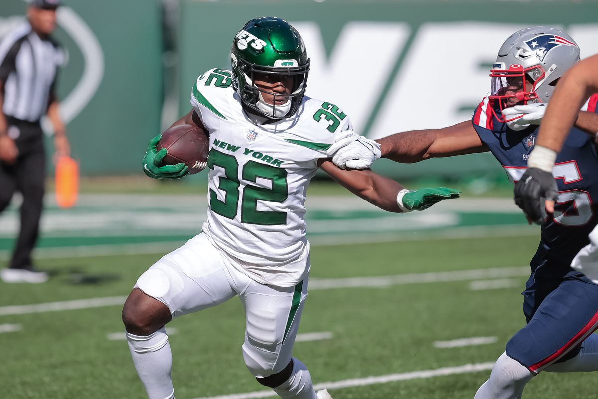 New York Jets running back Michael Carter (32) fights for yards against New England Patriots linebacker Josh Uche (55) during the second half at MetLife Stadium.