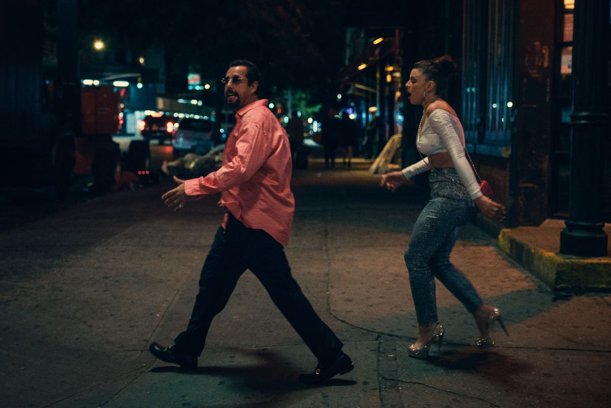 howard (adam sandler) and julia (Julia Fox) walk across the street in their club clothes