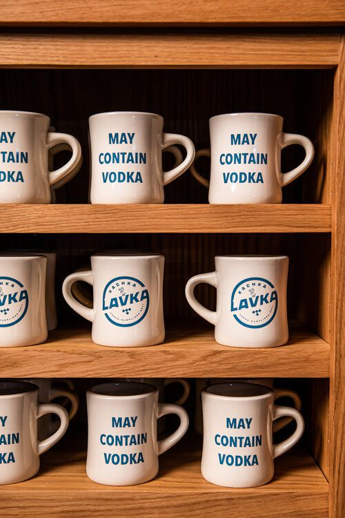 "Three shelves of mugs lined up, reading ""kachka lavka"" or ""may contain vodka"" on them"