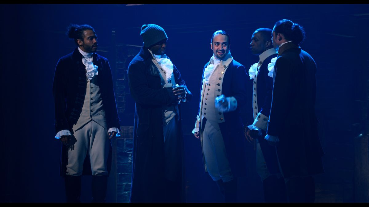 A group of cast members stands around Lin-Manuel Miranda in Hamilton.