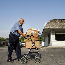 Ibdul Barzenji walks with a cart of food that he just received at the Mosaic Inter-Faith center in Salt Lake City on Thursday, Aug. 4, 2016.