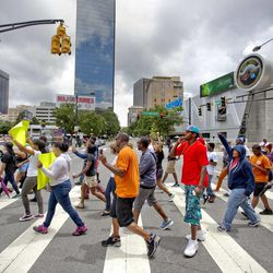 Demonstrators cross Marietta Street as they march in protest the day after George Zimmerman was found not guilty in the 2012 shooting death of teenager Trayvon Martin, Sunday, July 14, 2013, in Atlanta. (AP Photo/David Goldman)