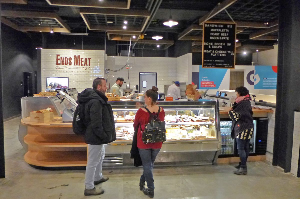 A few people stand facing a brightly lit butcher counter in a food court that has lots of empty spaces.