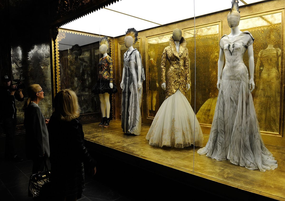Two visitors look at a series of McQueen dresses behind glass.