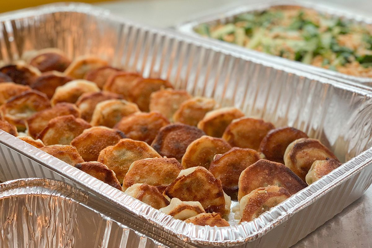 A large aluminum rectangular tray holds lines of pan-seared, Chinese-style dumplings