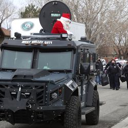 Santa rides in an armored West Valleypolice vehicle as officers deliver gifts to families during the department's Giving Tree event in West Valley City on Tuesday, Dec. 22, 2020. The program provided gifts for 159 children from 51 low-income families in the city that were delivered to their homes by police officers. Each child started with a list of needed items and holiday wishes. Santa's helpers from the police department, local businesses and the community then worked hard to fulfill the wishes.