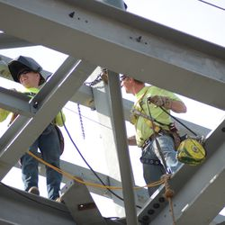 3:03 p.m. Welders working at the top of the video board structure -