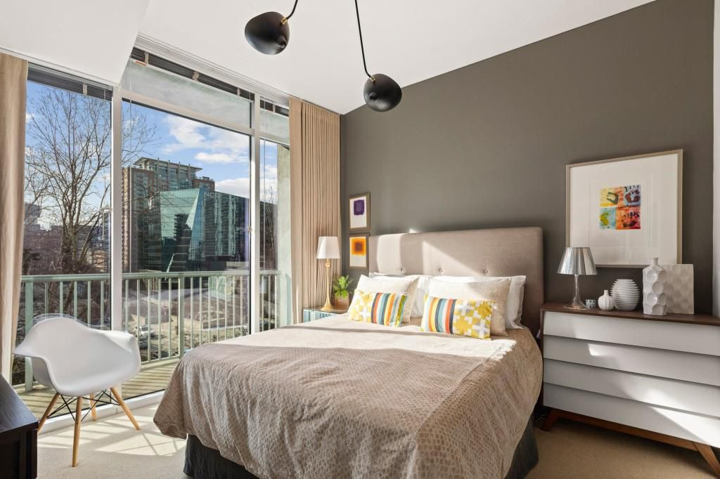 A bedroom with a huge window and doors overlooking a city.