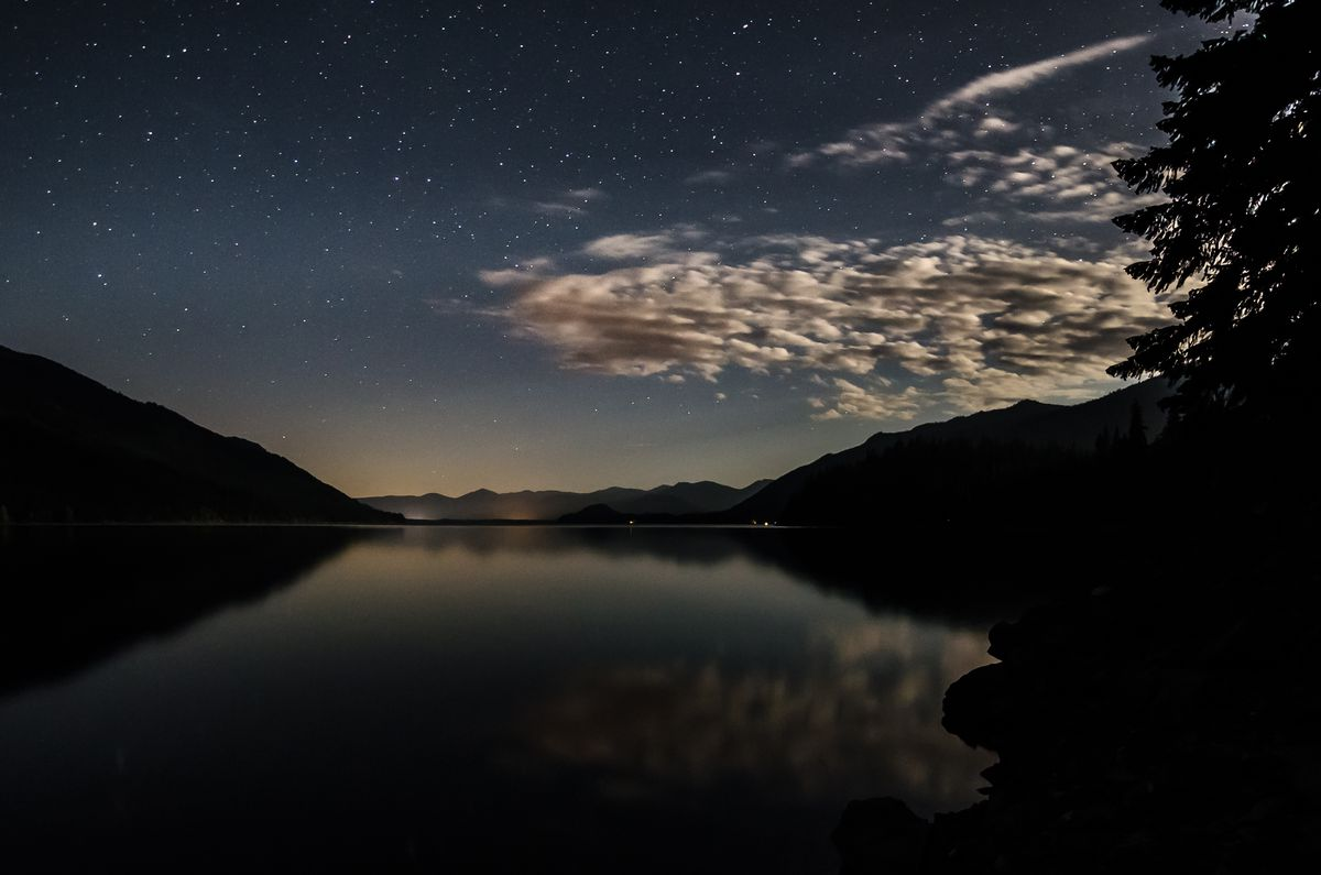 A night sky is full of stars, with a small collection of clouds emerging from the left. The sky and clouds are reflected on water below, surrounded by silhouettes of mountains and an evergreen tree.