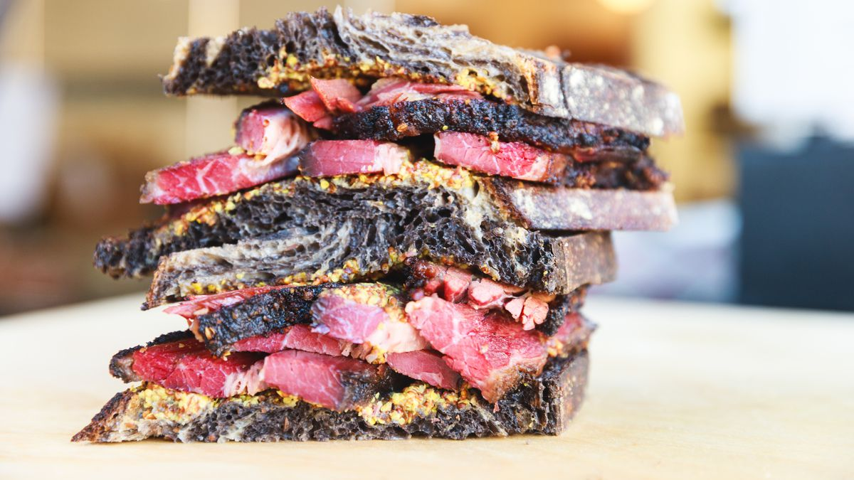Two thick pastrami sandwiches stacked on top of each other.