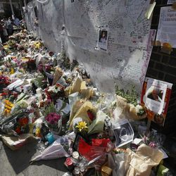 People look at flowers and messages left near Grenfell Tower in London, Saturday, June 17, 2017. Police Commander Stuart Cundy said Saturday it will take weeks or longer to recover and identify all the dead in the public housing block that was devastated by a fire early Wednesday.