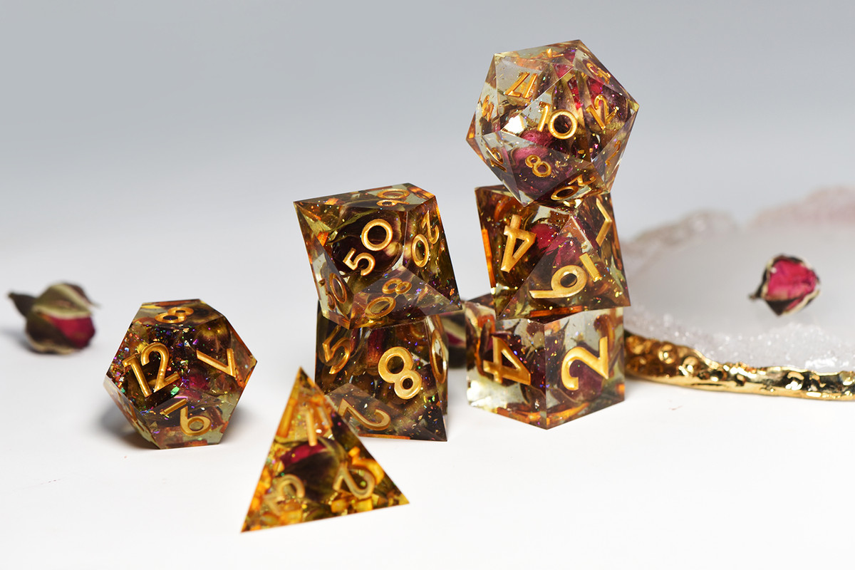Dice with multiple inclusions, including small roses and gold flake, set on a white background.