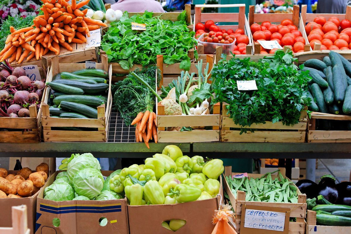 A selection of vegetables in wooden boxes, including tomatoes, cucumbers, and cabbage.