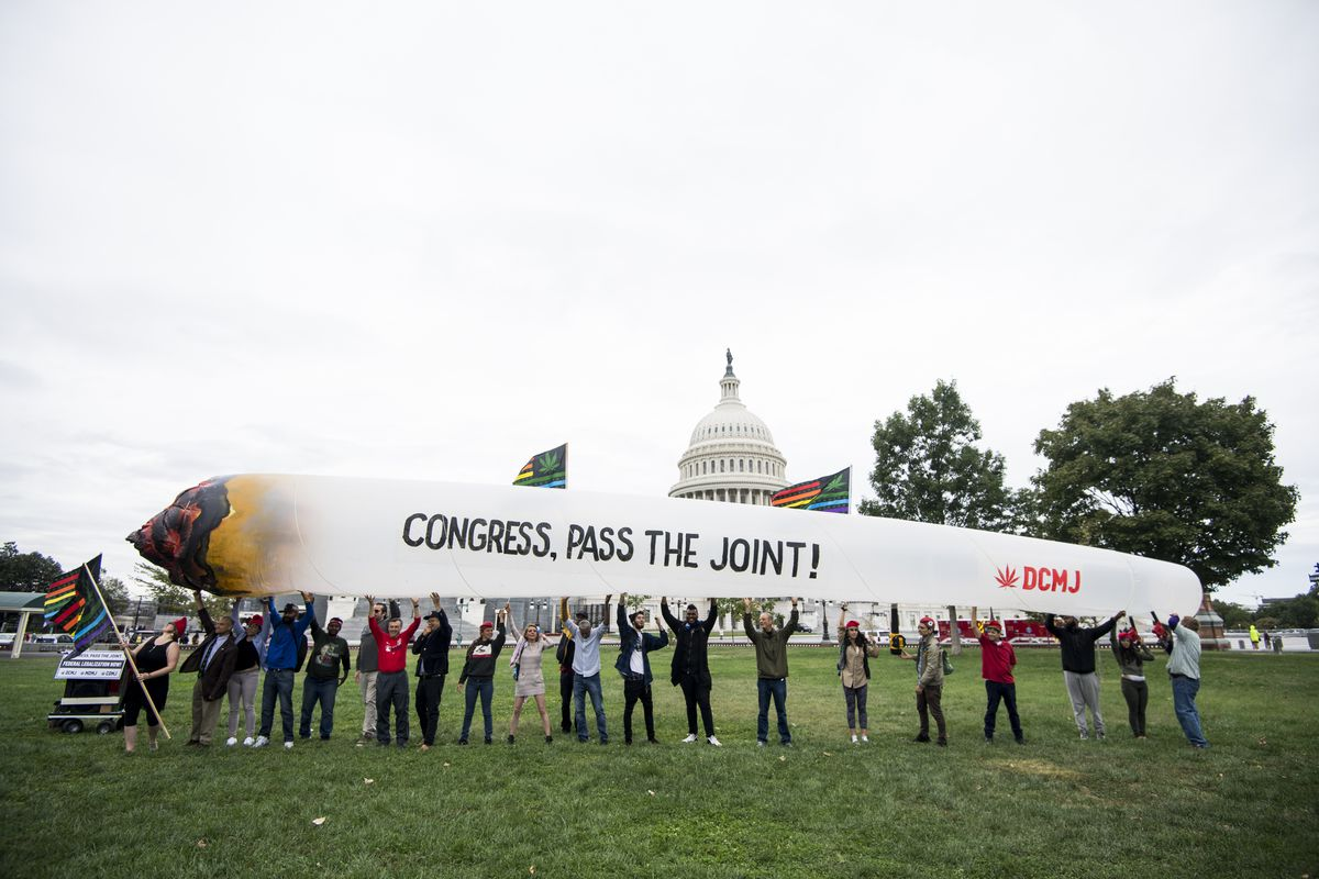 """Marijuana activists hold up a giant inflatable cigarette sporting the words, """"Congress, pass the joint!"""""""