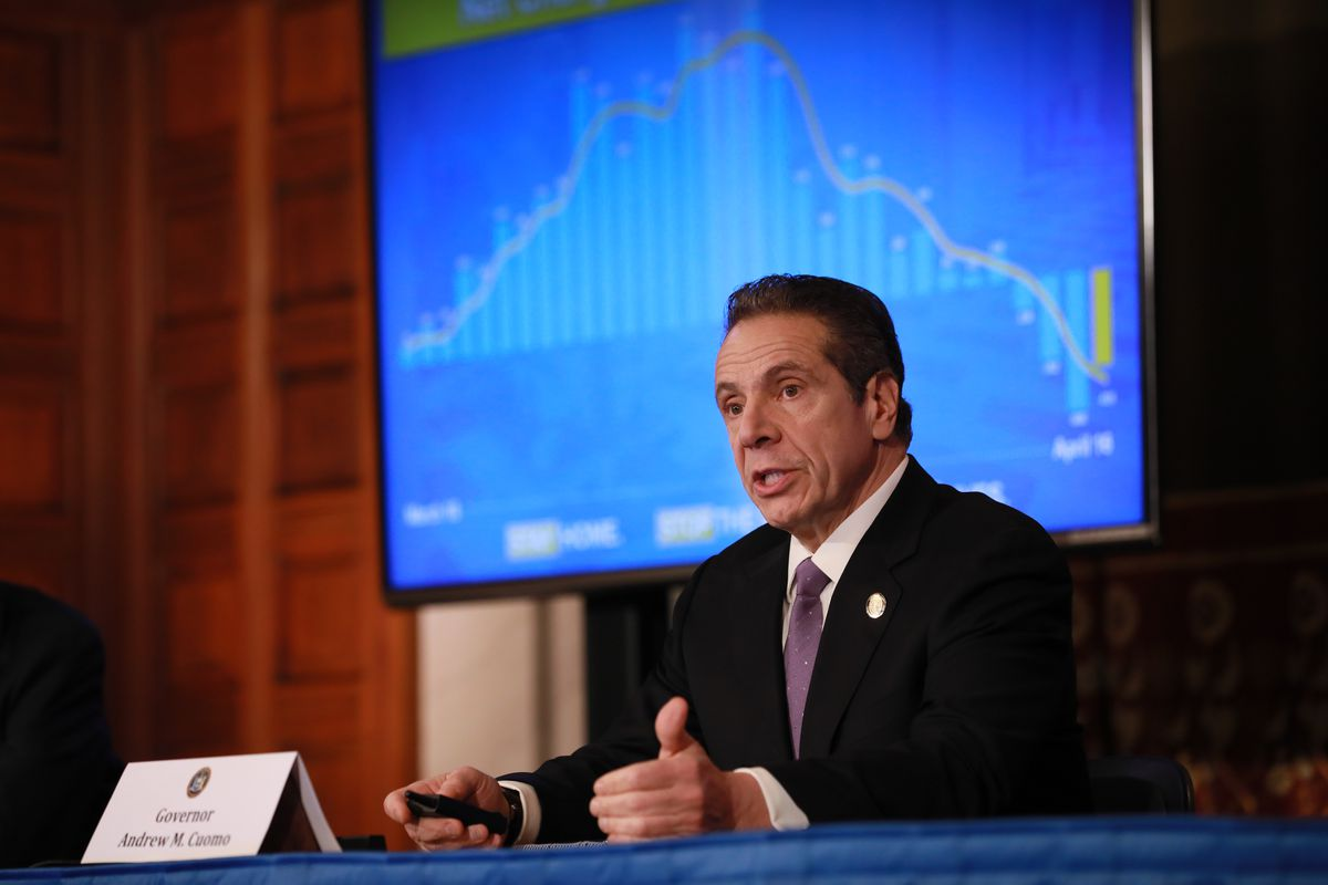 Gov. Andrew Cuomo speaks in front of a background depicting the curve of Covid cases.
