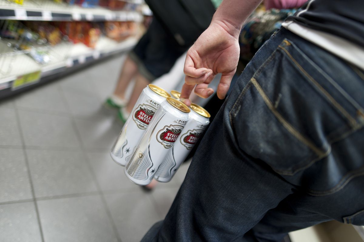 Young person buying a four pack of lager in a supermarket.