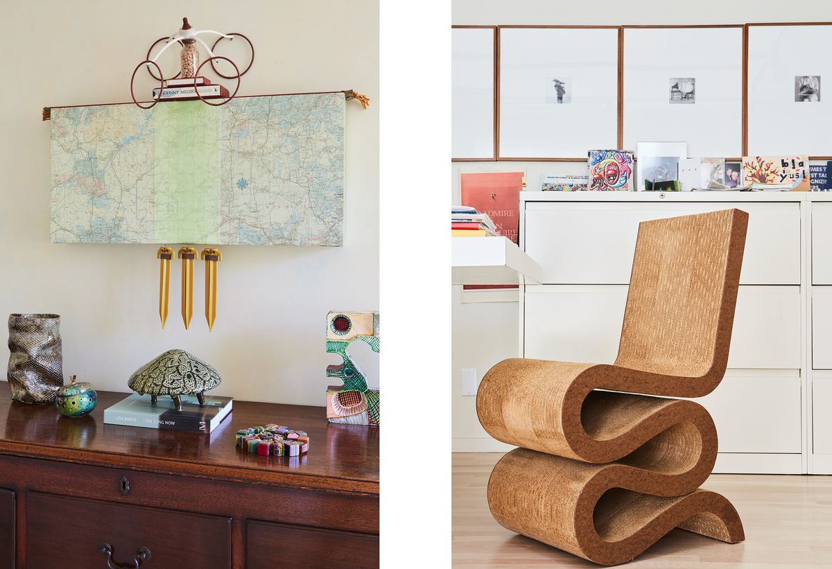 Bookshelves are stuffed with art books; Merry Norris stands in front of a colorful, abstract painting; she has another prototype of a Frank Gehry cardboard chair; a sculpture by Chris Finley hangs above a brown wood dresser.