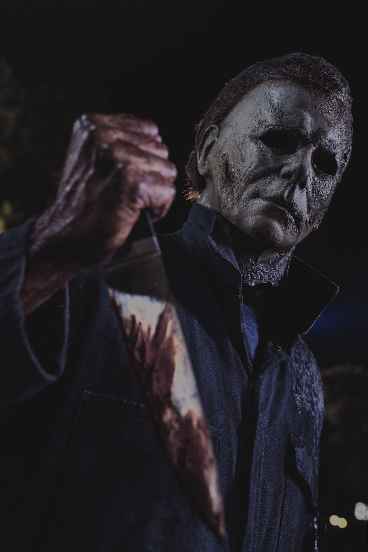 Michael Myers in a dirty mask holds up his bloody knife in Halloween Kills