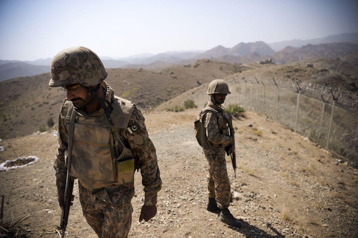Pakistani soldiers patrol next to a newly erected border fence along Afghan border at Kitton Orchard Post in North Waziristan on October 18, 2017.