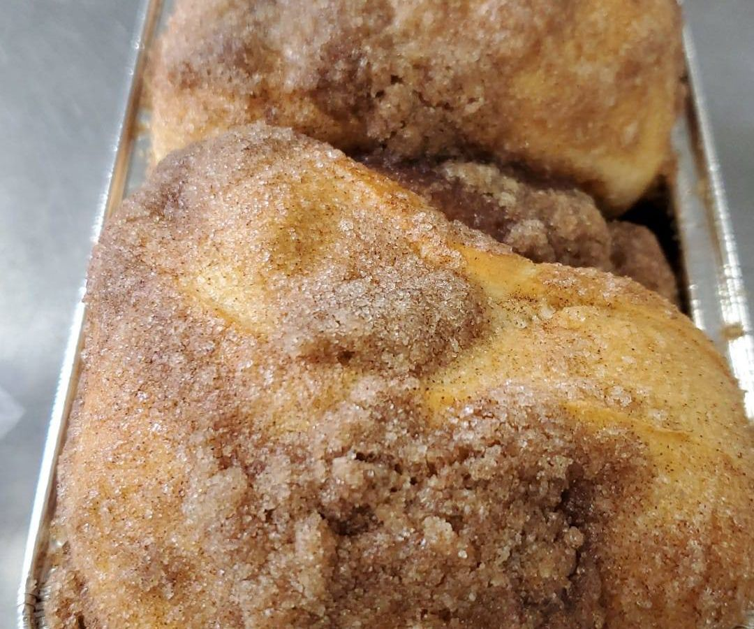 A pan of freshly baked cinnamon bread, topped with a crumbly mixture of cinnamon and sugar.