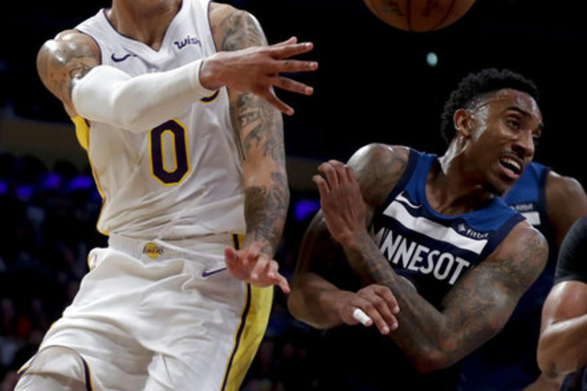Los Angeles Lakers forward Kyle Kuzma, let, passes around Minnesota Timberwolves guard Jeff Teague during the second half of an NBA basketball game in Los Angeles, Monday, Dec. 25, 2017. (AP Photo/Chris Carlson)