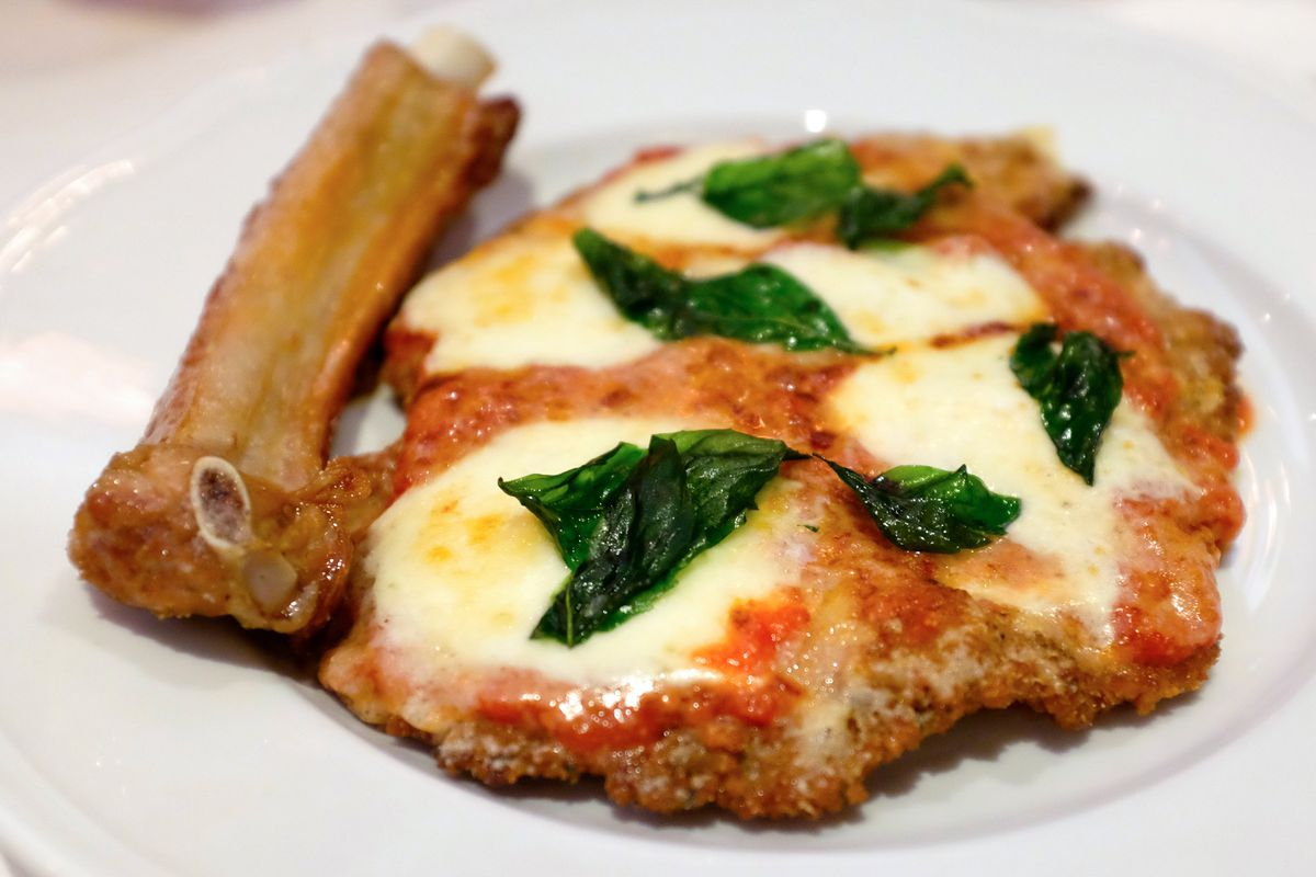 Carbone's veal parm, garnished with fresh mozzarella and basil, sits on a white plate