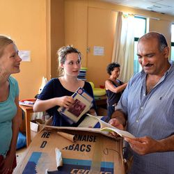 Farez Al-Hamdan, right, sorts through book donations with Catriona Franck, center, and another volunteer at the Kyllini refugee camp in Myrsini, Greece, July 11, 2016. The camp was previously a luxury resort before it fell into disrepair and was later turned into a refugee camp.