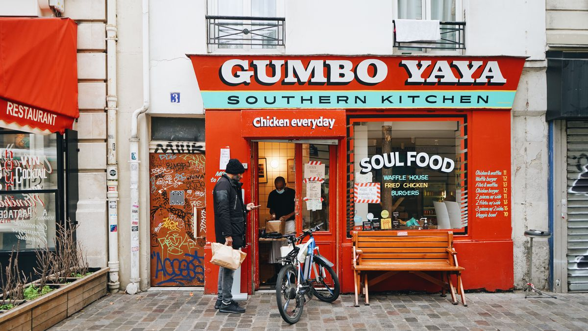"""A man stands next to a bicycle in the brick plaza outside of Gumbo Yaya as another man inside the doorway packs up some food. The restaurant's bright-red facade says """"Gumbo Yaya Southern Kitchen"""" and its front window reads """"Soul Food."""""""