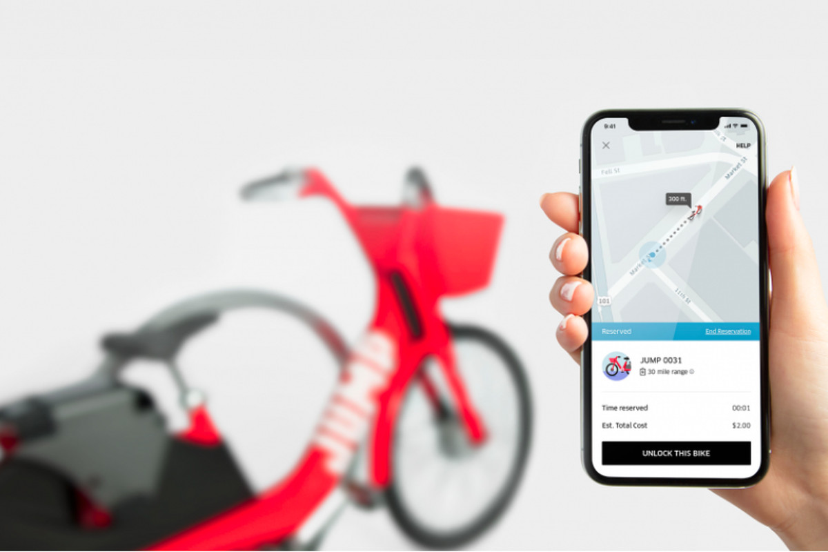 A mobile phone shows UberBike service in the Uber app, with an Uber Jump bike parked in the background.