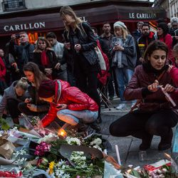 Mourners leave flowers, candles in front of Le Petit Cambodge, across the street from Le Carillon